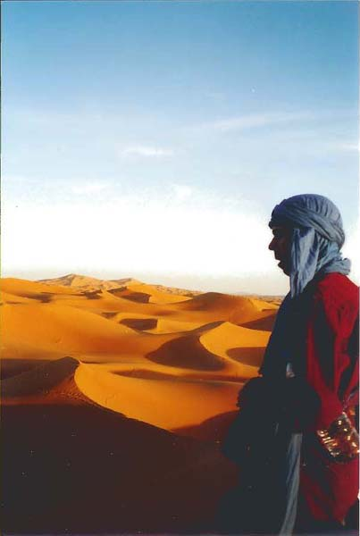 Dusk, and traveller contemplates the vast ruddy desert stretching to greet the cobalt blue sky at the horizon, by Weitzer