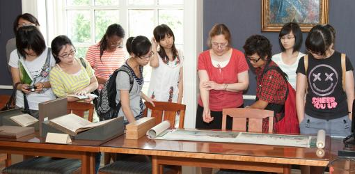 Librarian Holly Snyder shows students from Hong Kong a few of the Hay Library's treasured items about China.