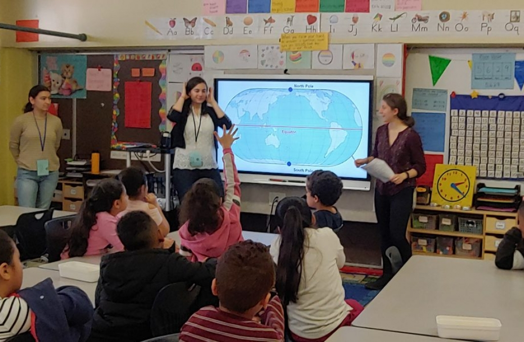 A student raising her hand in a classroom with three teachers at the front