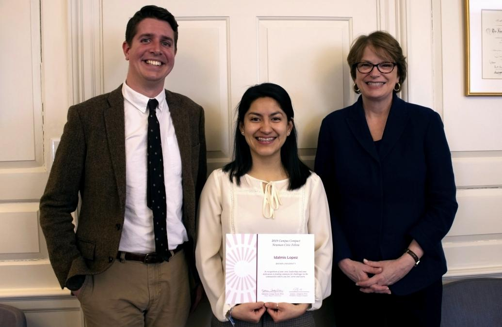 Idalmis Lopez stands holding her certificate. On her left is Andrew McQuaide, Senior Director at Perspectives Corporation, and on her right is Brown University President Christina Paxson.