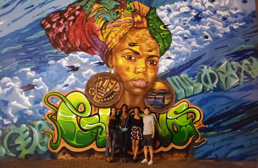 Blessed Sheriff and colleagues stand in front of a wall mural in Accra, Ghana