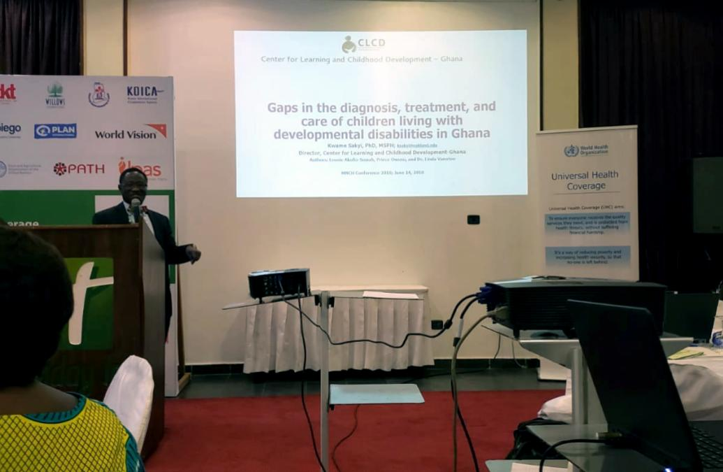 """A presenter speaks next to a large screen at the Maternal Newborn Stakeholder's Conference. The screen reads """"Gaps in the diagnosis, treatment, and care of children living with developmental disabilities in Ghana"""""""