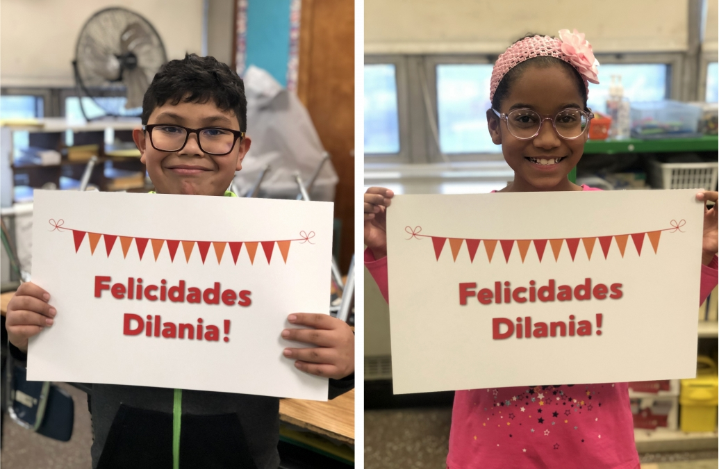 "Two students holding signs that read ""Felicidades Dilania!"""