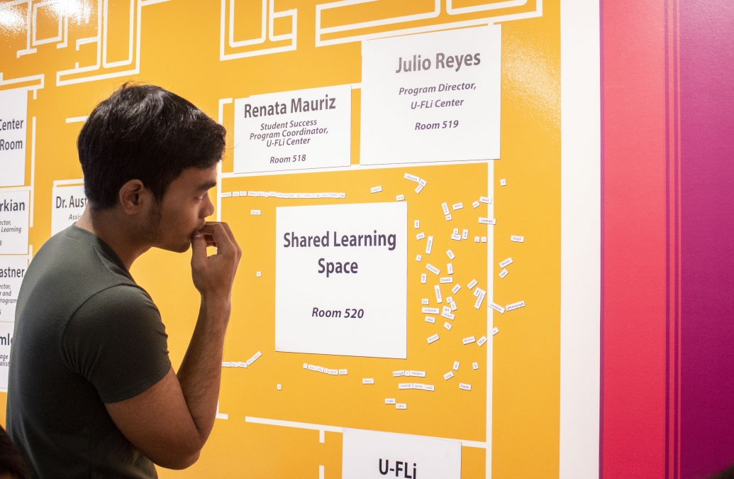 "A YSEALI fellow studies a yellow display that reads ""Shared Learning Space"""