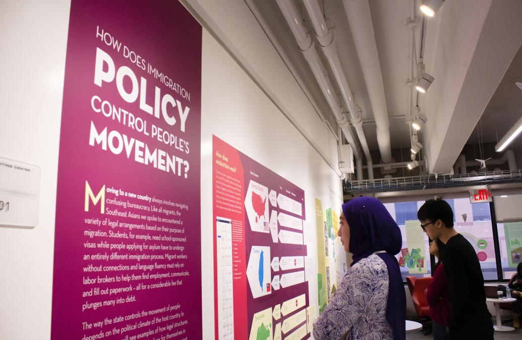 "Two YSEALI fellows studies a wall display in an exhibition that reads ""How does immigration policy control people's movement?"""
