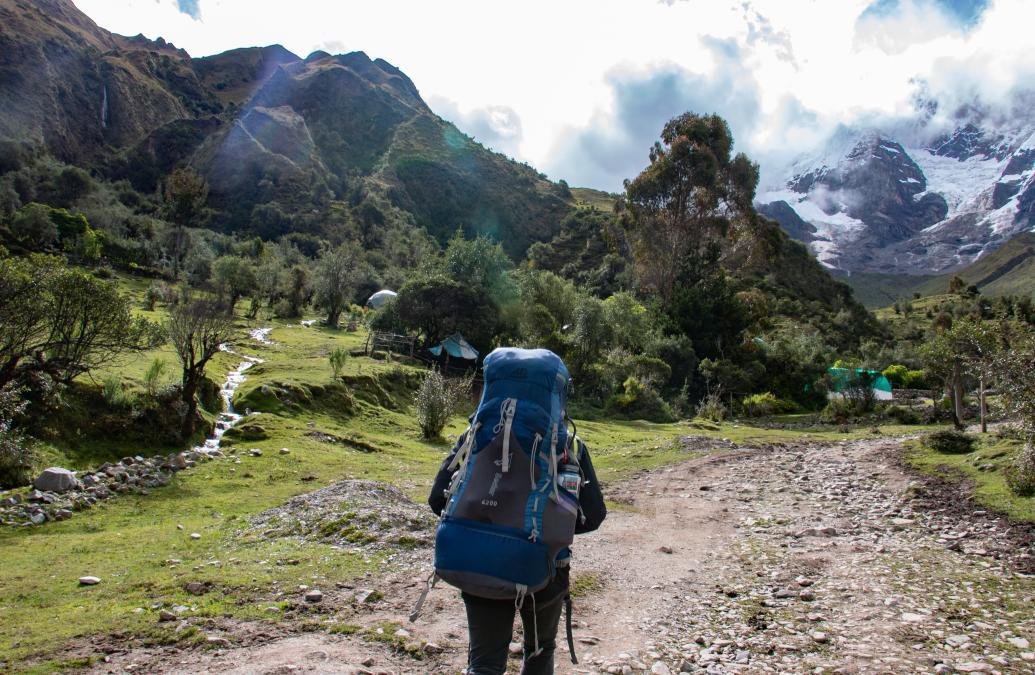 A backpacker walks towards a snowy mountain range in Bolivia