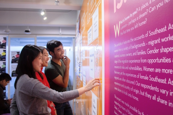 Three YSEALI fellows study a bright pink and yellow wall display at the Science Center at Brown University.