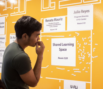 "A YSEALI fellow studies a bright yellow display which reads ""Shared Learning Space"""