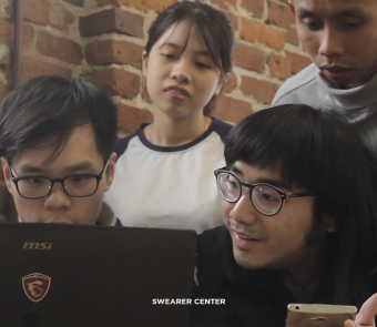 Four YSEALI Fall 2018 Fellows look at a laptop screen together.