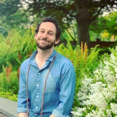 Ben Freeman portrait;  sitting in a garden smiling at the camera