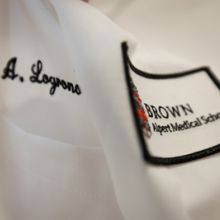 Image of white lab coat with medical school badge