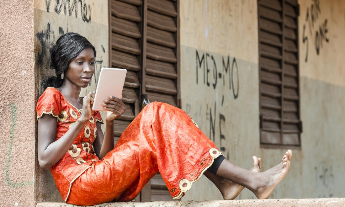 African young woman looking at electronic tablet