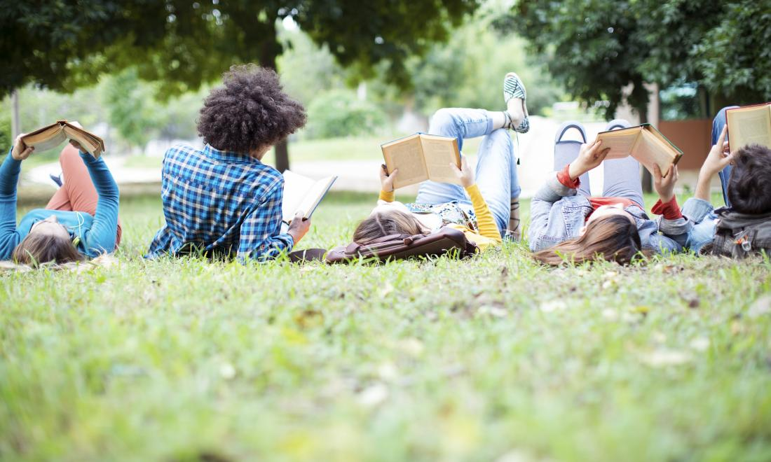 Five college students lying on lawn reading books