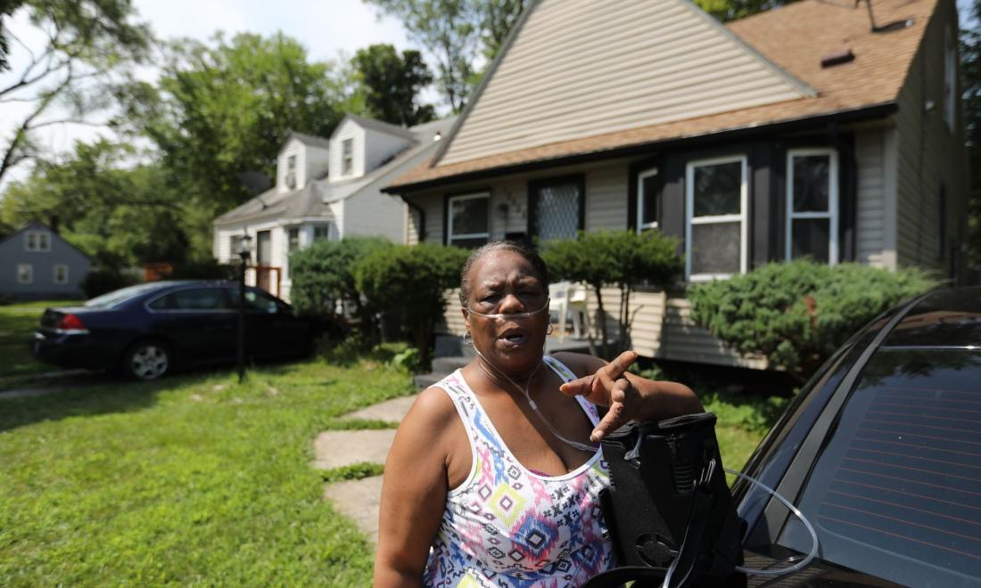 Woman stands in front of her home in Detroit