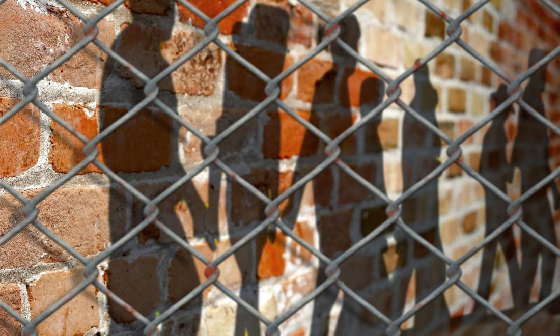 human shadows on a brick wall behind a chain link fence