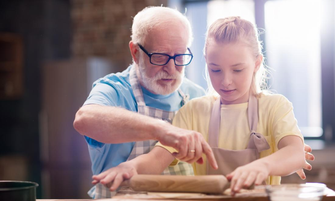 older gentleman and young girl baking together