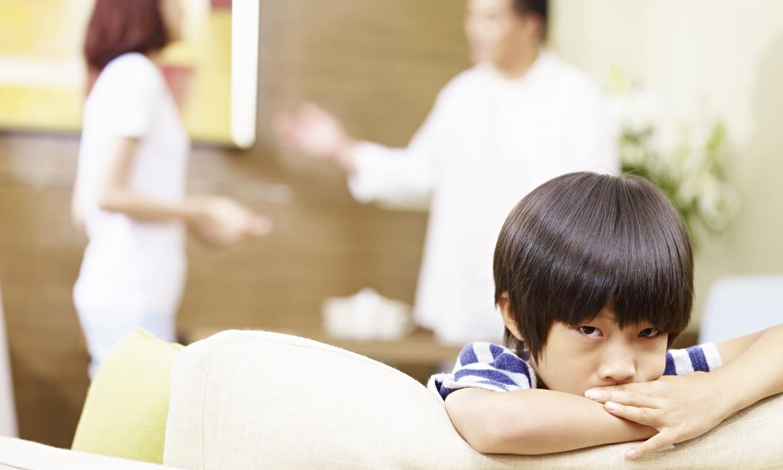 Japanese boy on sofa with parents fighting in the background