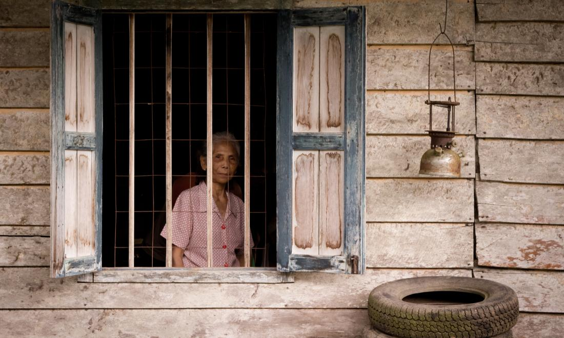 older Malaysian woman looking out window of wooden house
