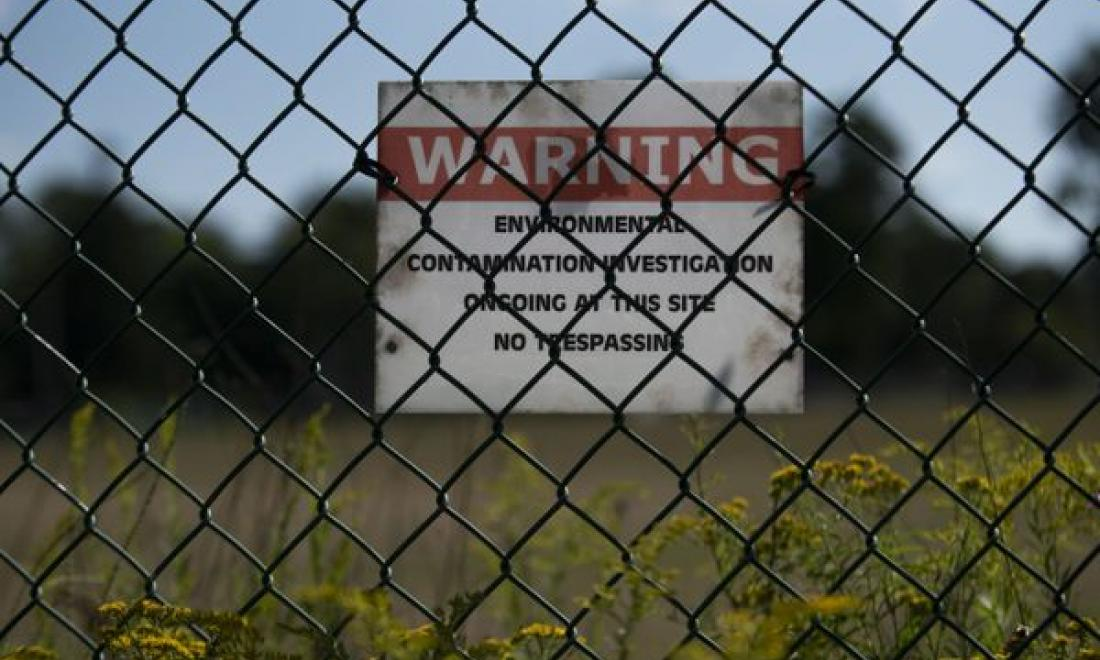 photo of fence with warning sign about environmental hazards