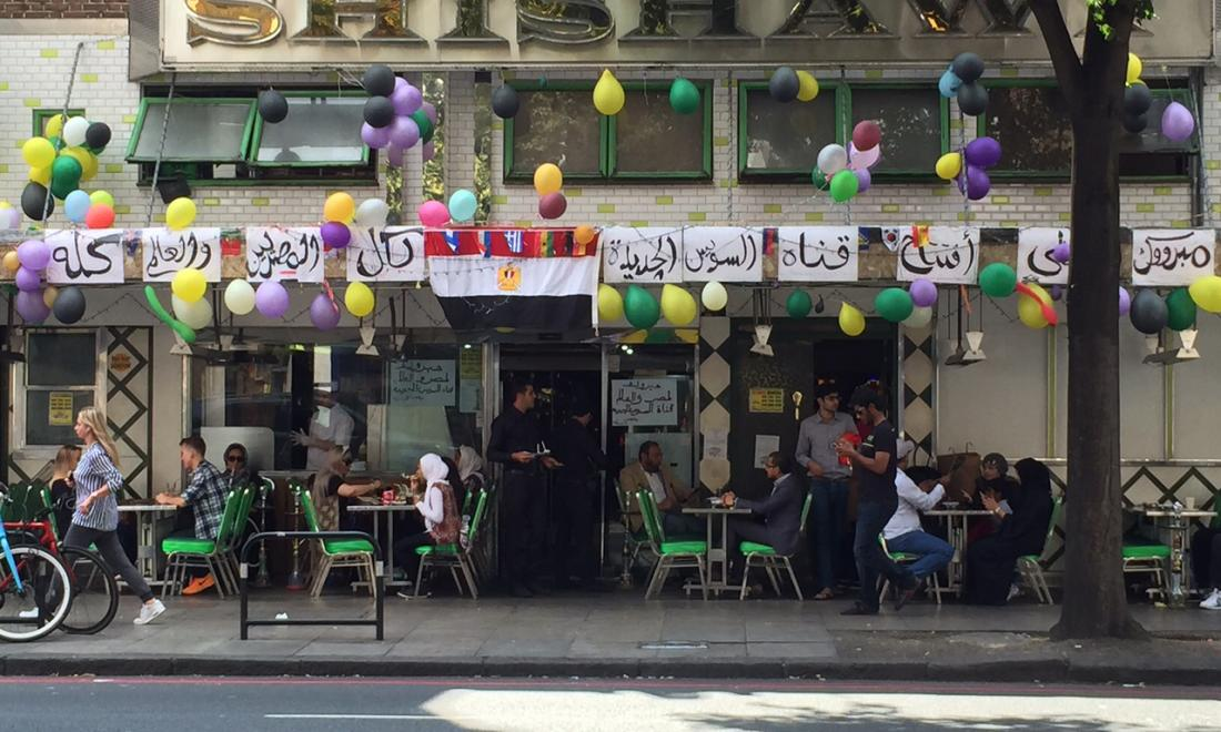 an outdoor cafe in Italy with arabic writing