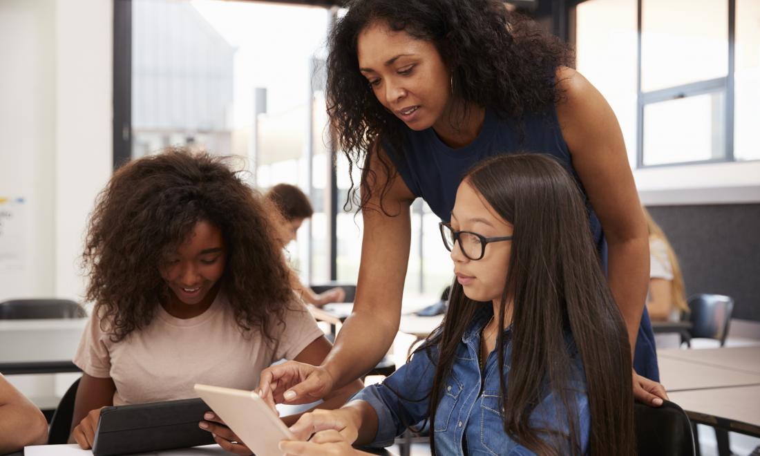 Teacher helps students in classroom