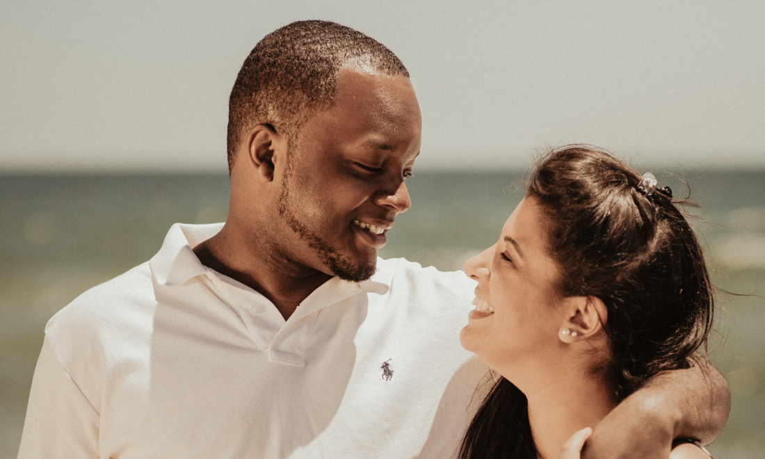 Interracial couple walking on beach.