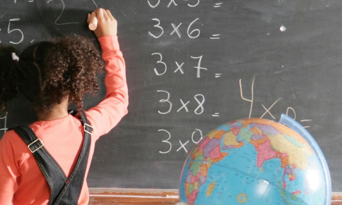 Student at chalkboard doing math