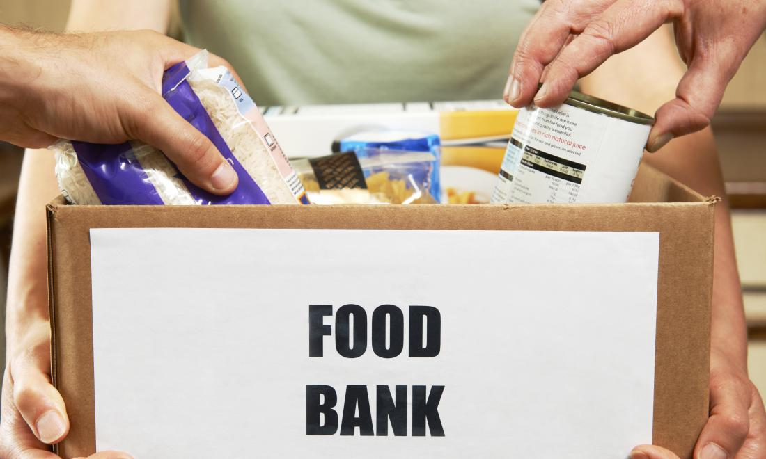 hands reaching in to take food items from a box labeled 'food bank'