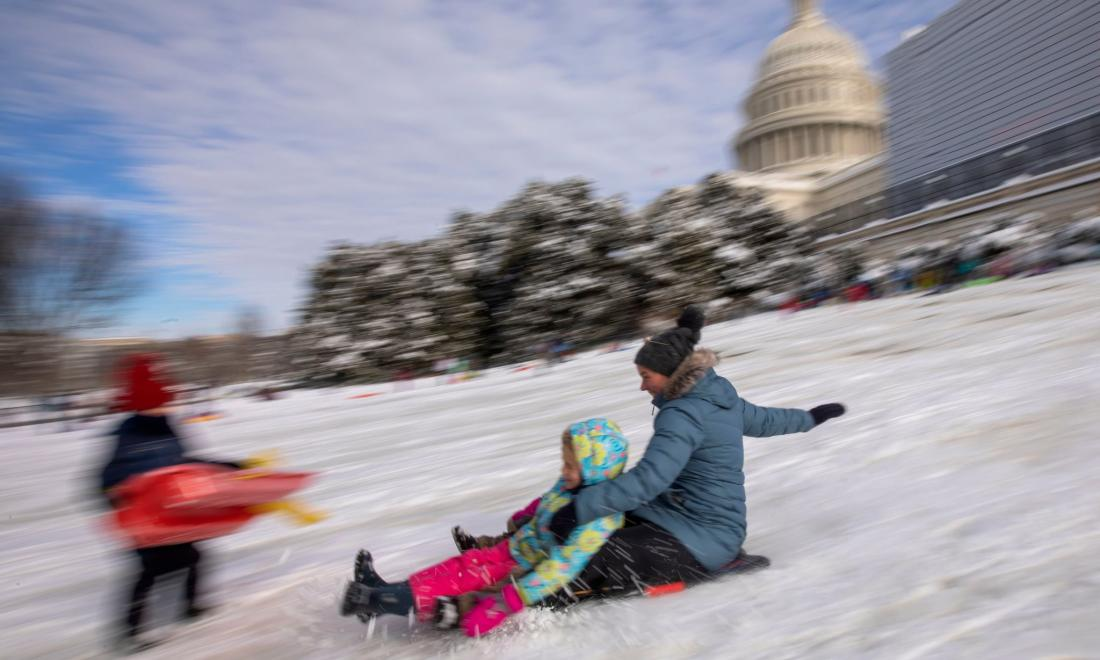 a mother and children sled near the US capital building