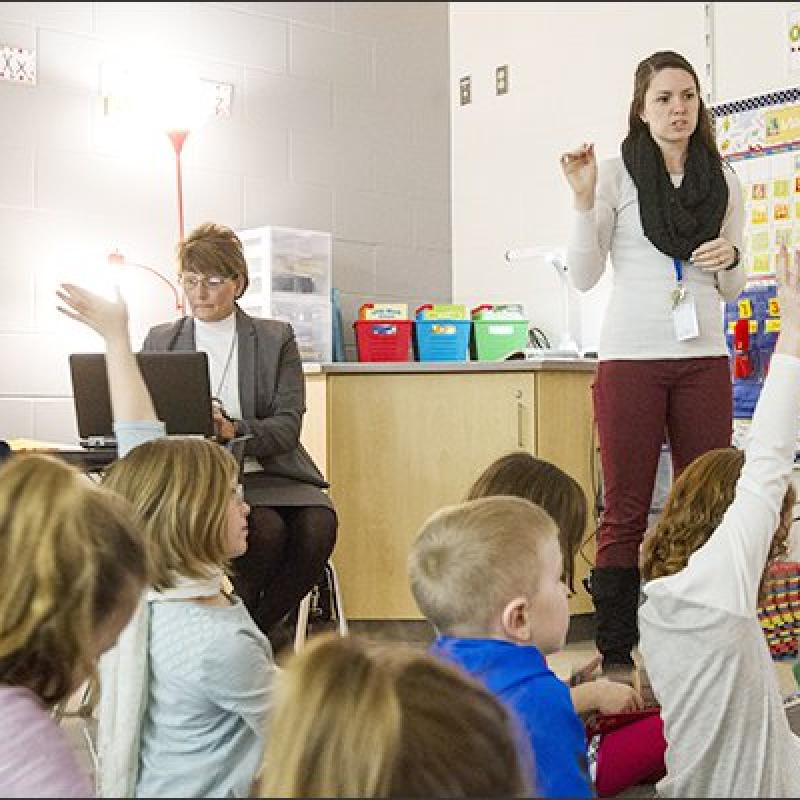 young teacher addresses elementary classroom while older teacher looks on
