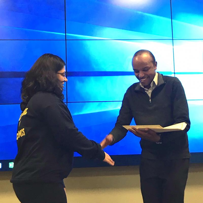 Kevin Mwenda presents Aditi Singh with her certificate of completion for the GIS Institute