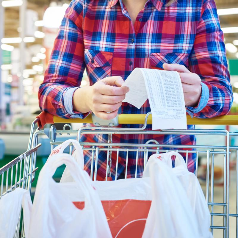 Women with cart full of grocery bags checks receipt