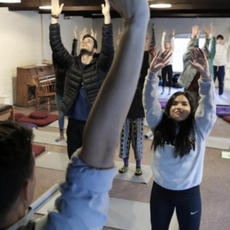 Class practices yoga and mindfulness techniques in a stress-reduction class