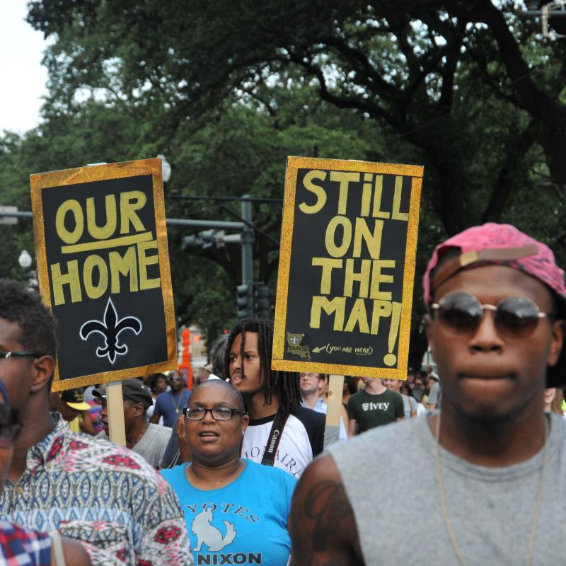 "Black residents of New Orleans march with signs saying ""Our Home"" and ""Still on the map"""