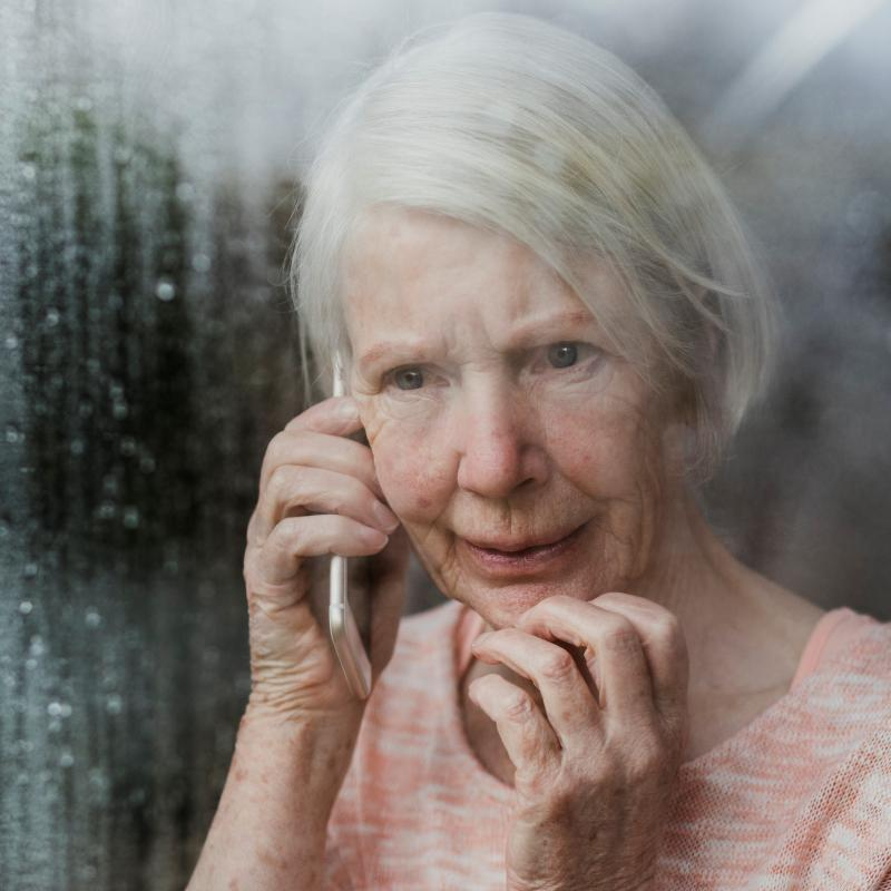 Older woman on talking on the phone at a raining window