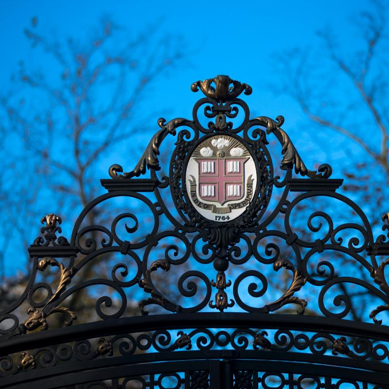 Brown logo at the top of the Van Wickle Gate on campus