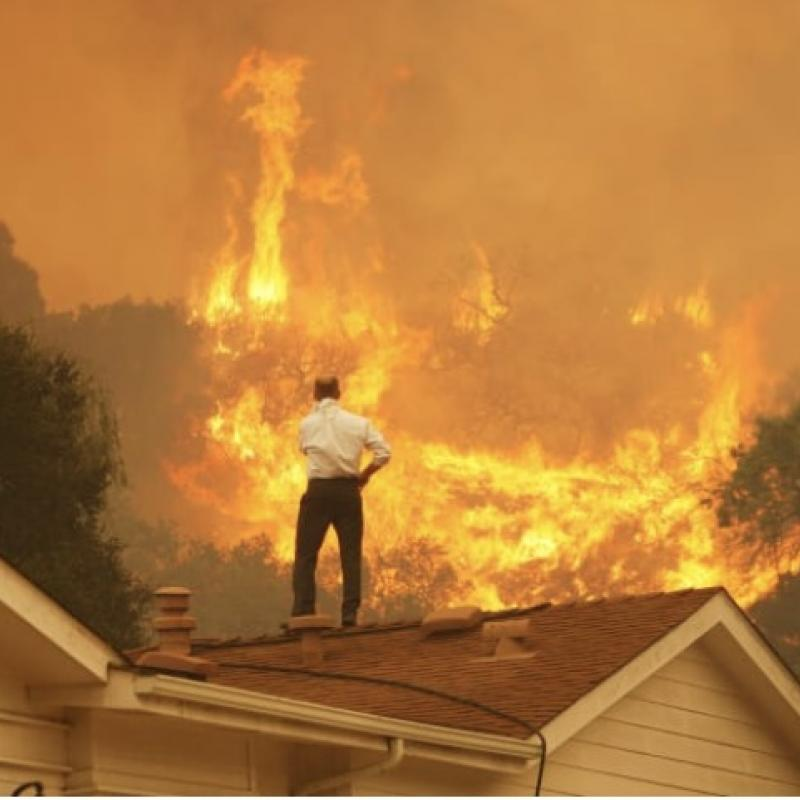 Man stands on house roof watching approaching wildfire