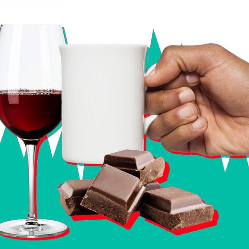 hand holding a coffee much surrounded by chocolate and a wine glass
