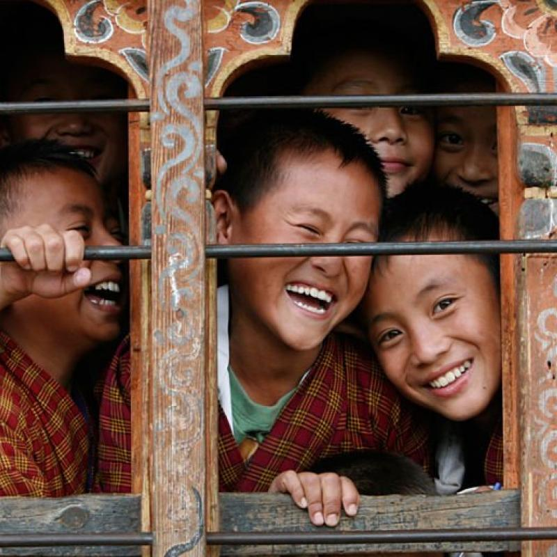 Schoolchildren react to the camera through the window of their classroom in a school in Thimphu, Bhutan