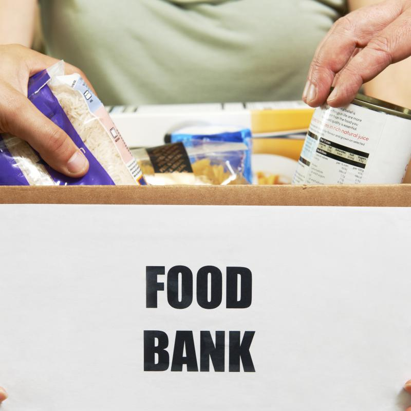 Box of food bank supplies with hands reaching for food items