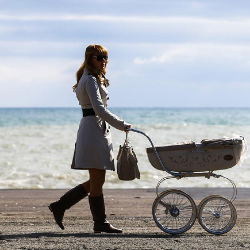 woman pushing baby carriage on beach