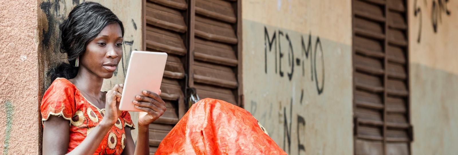 African young woman looks at electronic tablet