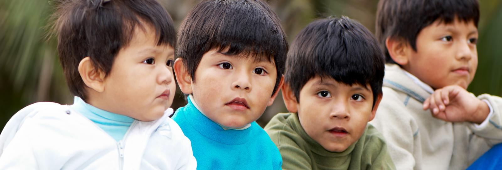 four young Latino brothers sitting in a row (toddler to elementary age)