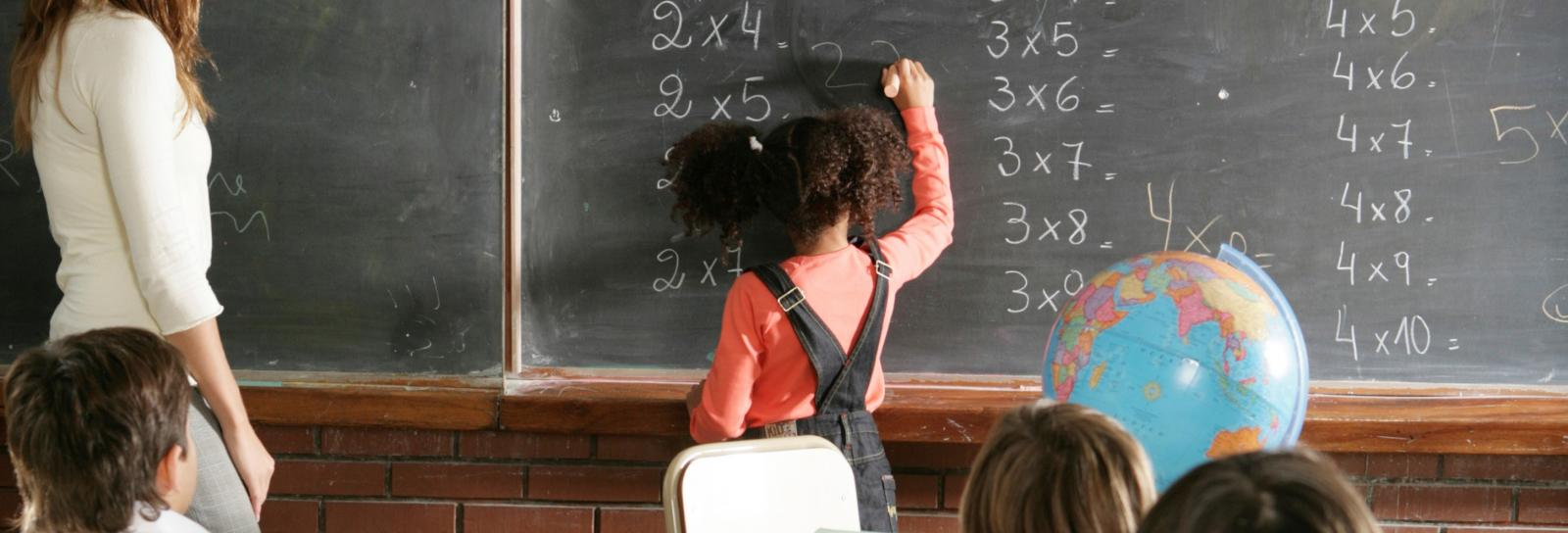 a young girl solves simple math problems on the black board while teacher and classmates watch