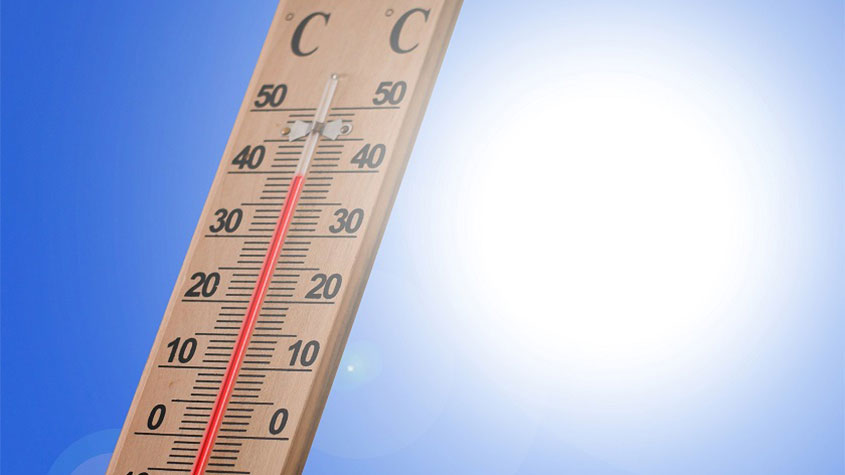 A thermometer against a backdrop of blue sky and a bright sun