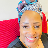picture of Gwendolyn-Purifoye sitting on a red couch with a multicolored headscarf