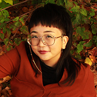 picture of Jina-B.Kim wearing a red sweater and black collar with trees and greenery in the background