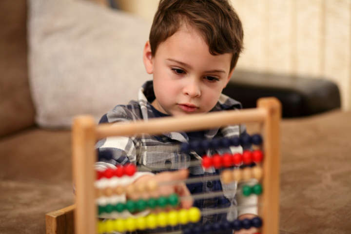 A child playing with an abacus